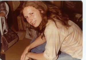 1970s person with long hair seated and turning sideways to look at the camers