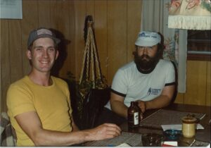 Two people at table: one on left has a yellow tshirt and baseball cap and one on right has white tshirt and cap
