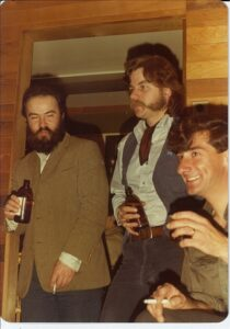 3 people standing and drinking beers: dark haired bearded person on left wearing brown sports jacket, dark haired person in middle with mutton chops, shirt and vest, person on right with dark hair and clean-shaven