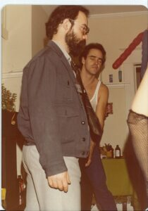 person with dark hair and beard wearing grey jacket, another person with dark hair wearing a tank top behind