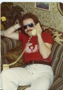 person with dark hair, mustache, white trousers and red tshirt sitting on couch and talkin on phone