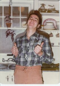 Person with dark hair, plaid shirt and brown trousers standing in front of kitchen sink giving a thumbs up