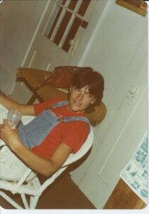 person with short dark hair wearing red tshirt, dunagrees, sitting in a chair