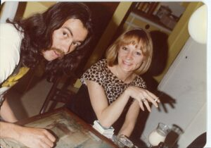 person with long dark hair and mustache leaning over table, person with strawberry blond hair wearing blouse sitting at table