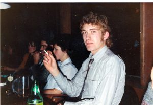 man with blond curly hair seated at dinner table