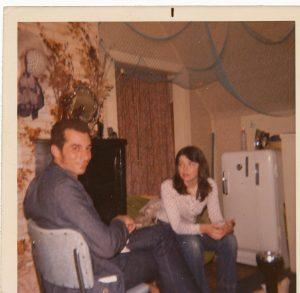 dark haired man and dark hair women sitting in house, fridge behind